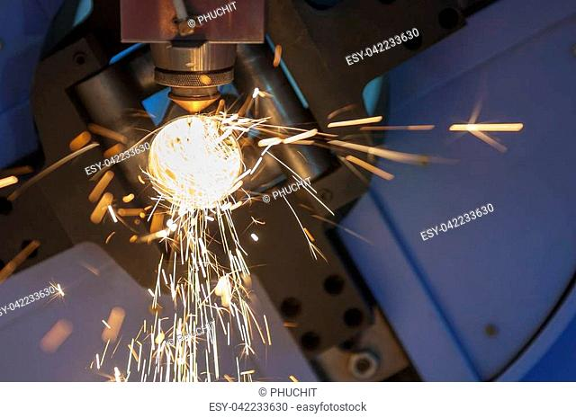 The fiber laser cutting machine cutting the stainless pipe with the sparking light