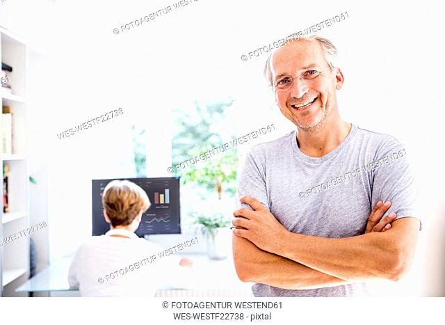 Portrait of smiling senior man with wife in background using computer