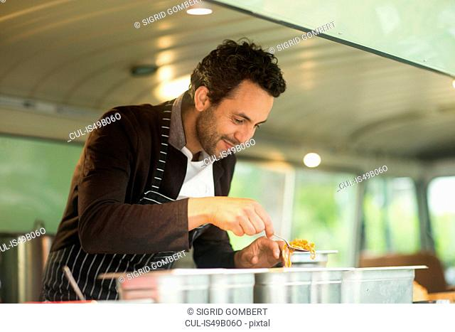 Small business owner serving food from van food stall hatch