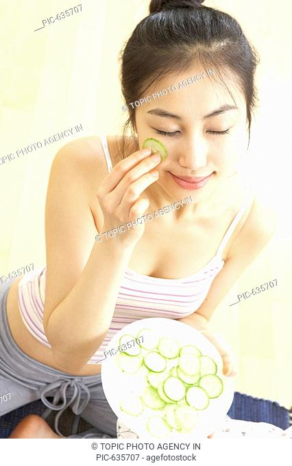 Young Korean Woman Doing Facial Massage with Cucumber Slices