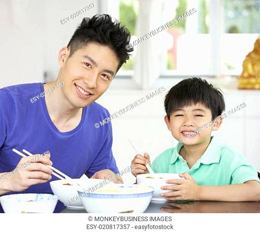 Chinese Father And Son Sitting At Home Eating A Meal