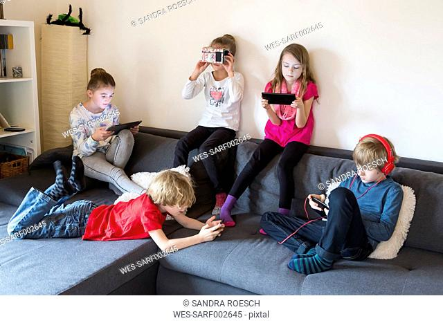Five children on a couch using different digital devices