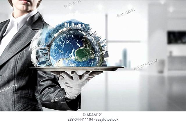 Cropped image of waitress's hand in white glove presenting Earth globe with buildings on metal tray with office view on background. 3D rendering