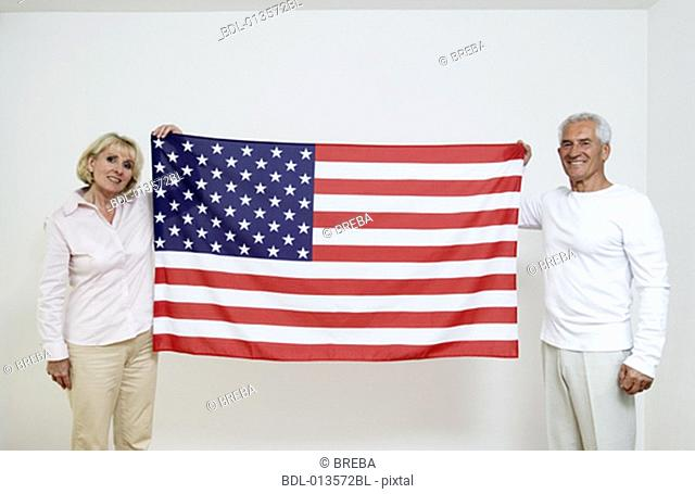 two mature people showing American flag, the Stars and Stripes