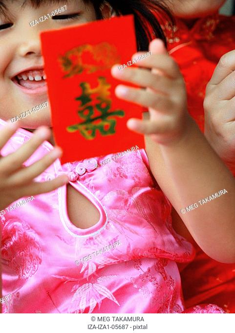 Close-up of a girl holding a red gift packet Hong Bao with her mother