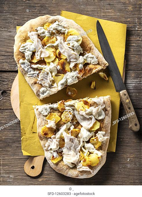 A rustic pizza with potatoes, rosemary and lardo