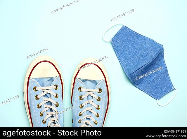 reusable textile mask and blue sneakers on a blue background, safe walks during a viral pandemic, top view, flat lay