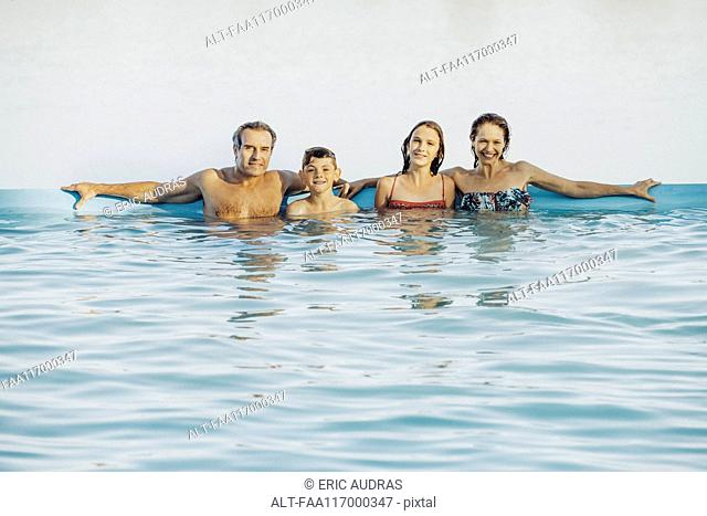 Family leaning against poolside