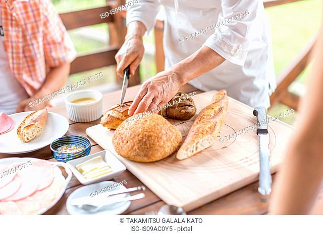 Woman cutting baguette