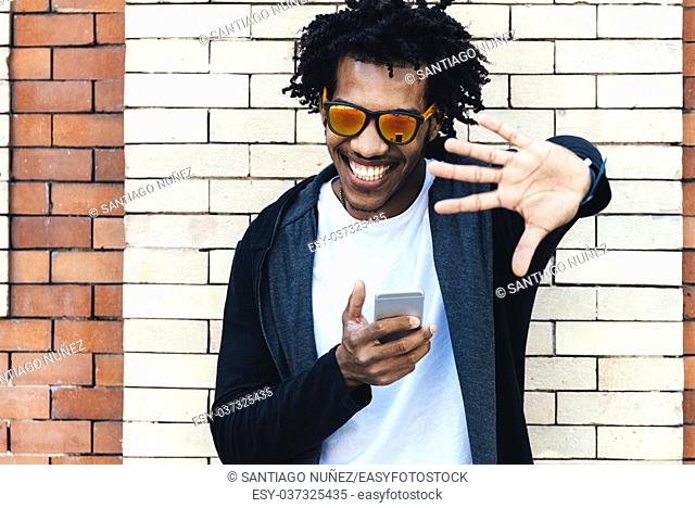 Portrait of afro handsome man using his mobile in the street