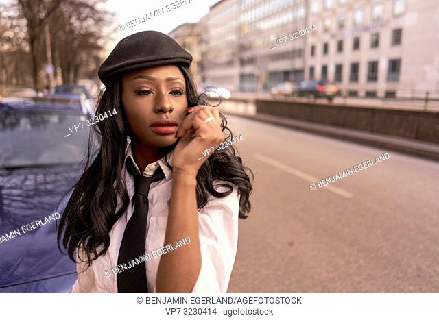 stylish emotional woman in evening sunlight at street, wearing retro business outfit, individual look, African Angolan descent, in city Munich, Germany