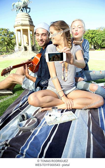 Happy friends in park taking a selfie