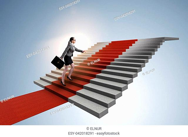 Young businesswoman climbing stairs and red carpet