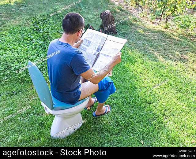 Funny quarantine moments - Man sitting on a toilet chair and reading newspaper outside in his garden
