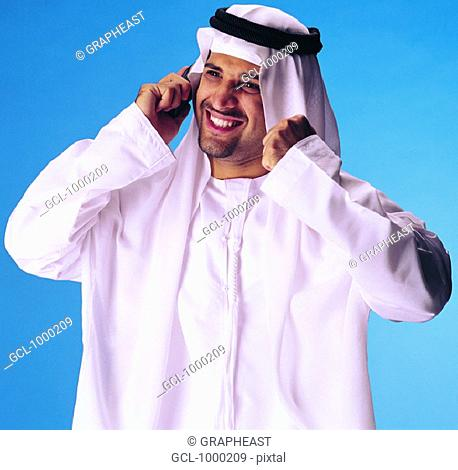 Arab man on cell phone with clenched fist