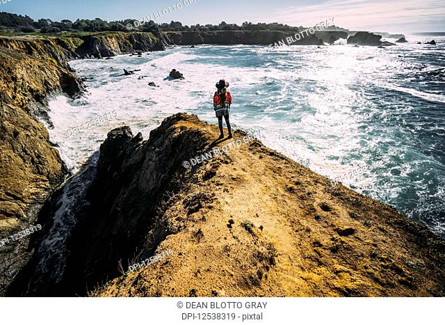 A woman stands looking out along the Russian Gulch Headlands, Mendocino county; California, United States of America