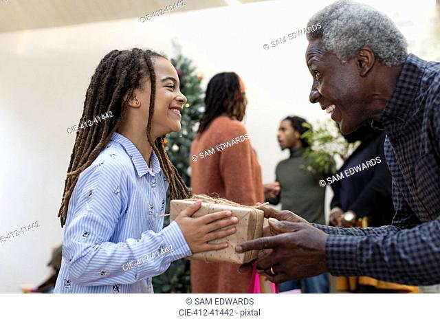 Happy grandfather giving Christmas gift to granddaughter