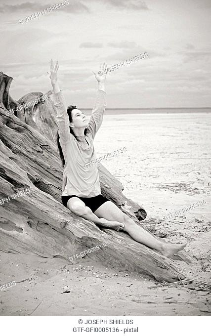Yoga instructor posing on large driftwood