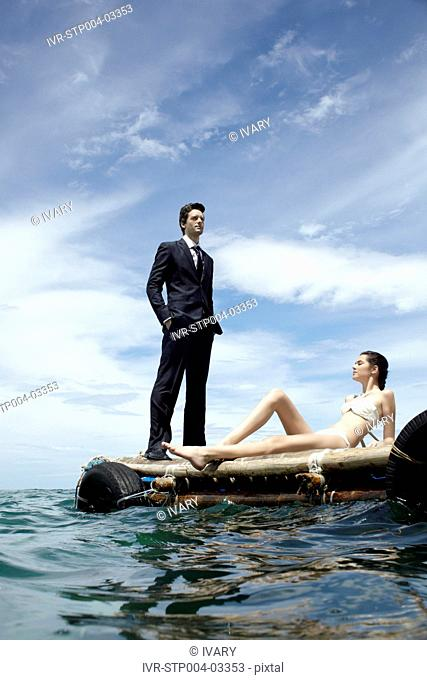 A businessman and a young woman posing on a dock