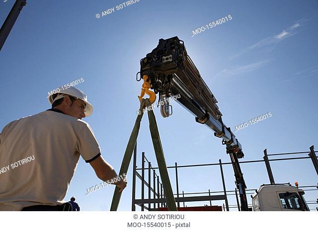 Unloading RSJs rigid steel joists from truck to build warehouse