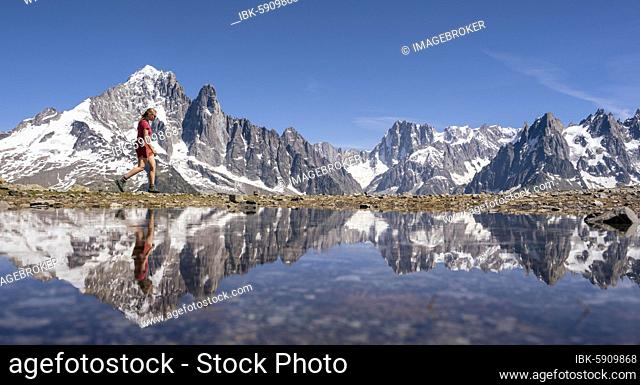 Young woman walking in front of mountain panorama, reflection in Lac Blanc, mountain peaks, Grandes Jorasses and Mont Blanc massif, Chamonix-Mont-Blanc