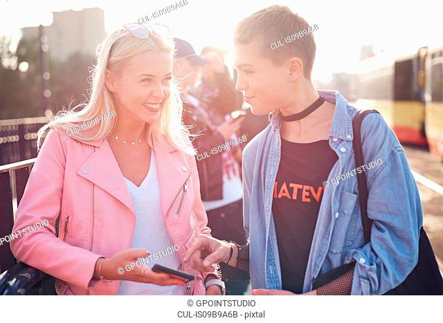 Two young female friends at sunlit city tram station