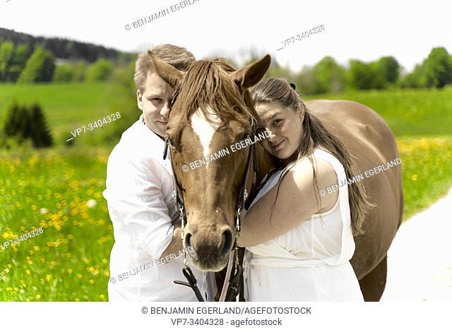 Couple with horses, in Wackersberg, Bavaria, Germany