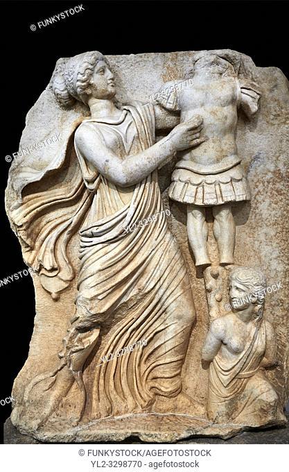 Roman Sebasteion relief sculpture of a Goddess inscribing a trophy, Aphrodisias Museum, Aphrodisias, Turkey. Against a black background.