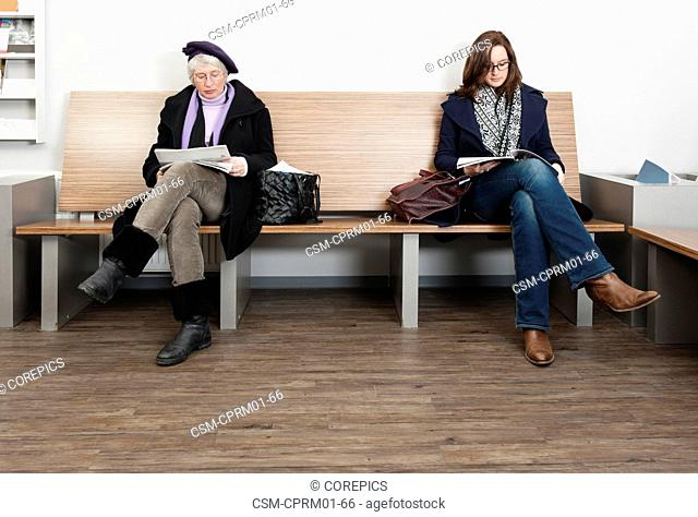 Two women, sitting in mirrored poses, in the waiting room of a general medical practice