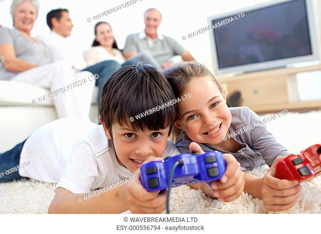 Children playing video games on floor and family sitting on sofa