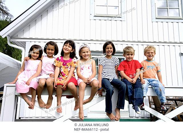 A group of children sitting in front of a house Sweden