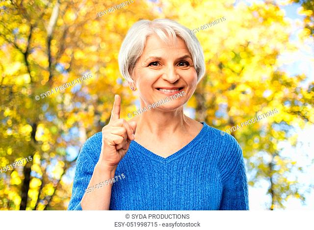 senior woman pointing finger up in autumn park