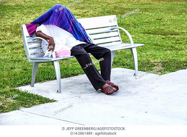 Florida, Miami Beach, Lummus Park, park bench, Black, man, sleeping, covered face, head, blanket, hiding, mental health illness, homeless, teen