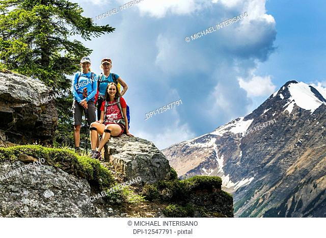 Three female hikers on a mountain rock with mountain and blue sky in the background; British Columbia, Canada