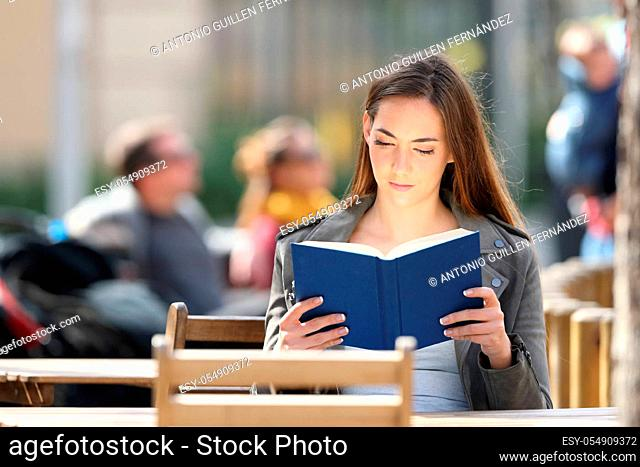 Front view portrait of a young woman reading a hard cover book on a coffee shop terrace a sunny day