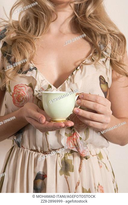 Close up of a woman holding a green teacup