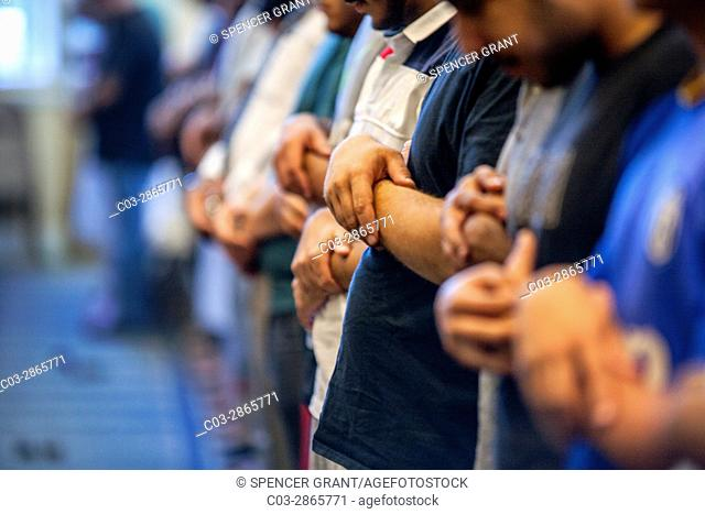 Muslim men of many ages gather for Friday afternoon prayers during religious services at an Anaheim, CA, mosque. Clasped hand position indicates Sunni Muslim...