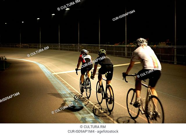 Cyclists cycling on track at velodrome, rear view