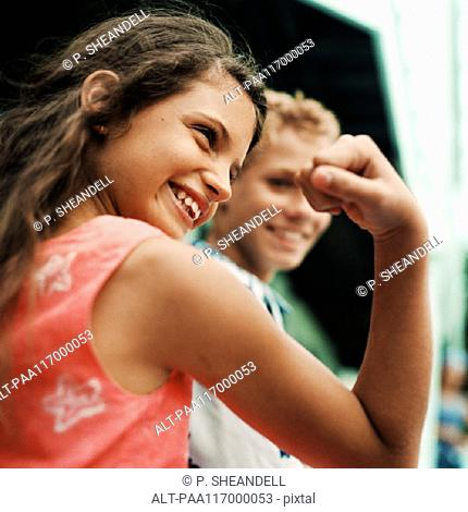 Girl flexing arm muscles, boy in background, smiling