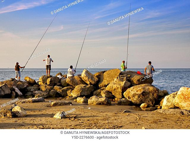 group of men fishing in traditional way - with fishing rods directly from Mediterranean Sea, beach in Montesilvano, province of Pescara, Abruzzo region, Italy
