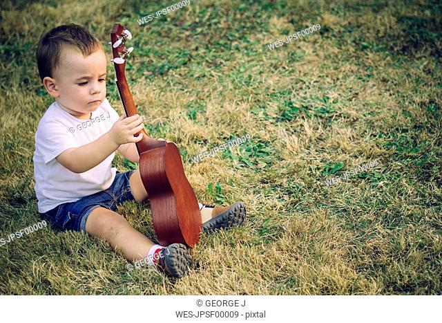 Baby boy sitting on a meadow with ukulele