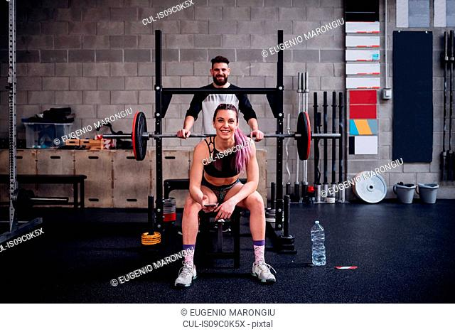 Young woman and man training together in gym, sitting on weight bench, portrait