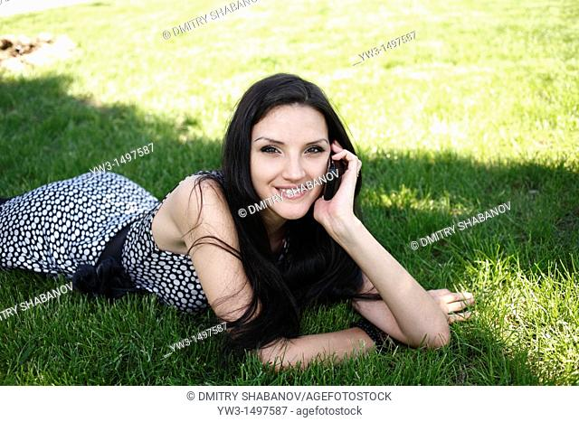 25 years pretty women outdoors on the grass with cell phone