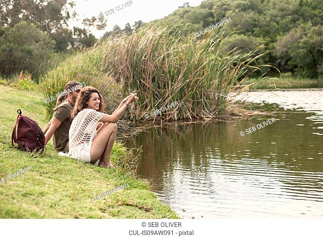 Couple sitting by river looking away smiling