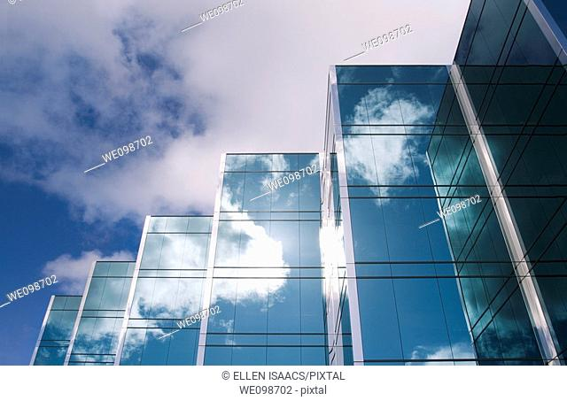 Five towers of a sleek modern glass office building in Silicon Valley with the clouds and sky reflecting on the surface of the buildings
