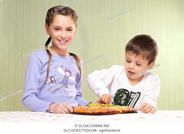 Girl and her brother eating a pizza
