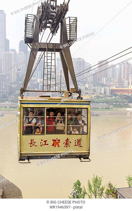 Passengers ride in a cable car over the Yangtze river, Chonqing, China
