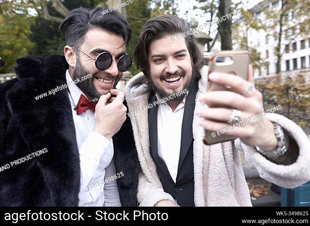 two men laughing about what they see on smartphone