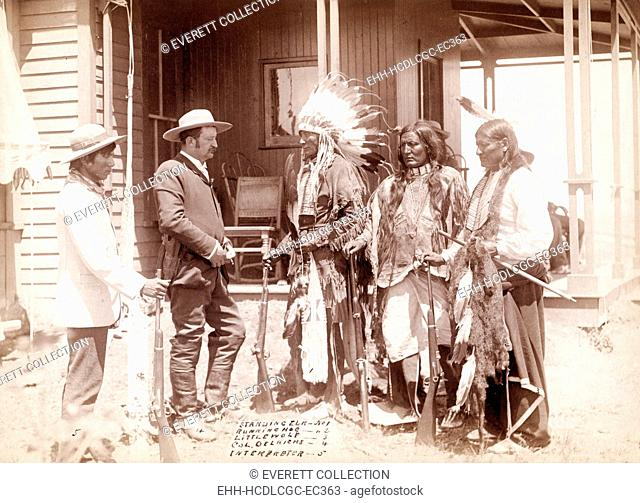 The Interview. Three Cheyenne men, Standing Elk, No. 1; Running Hog, No. 2; Little Wolf, No. 3, wearing ceremonial clothing and holding rifles with Col