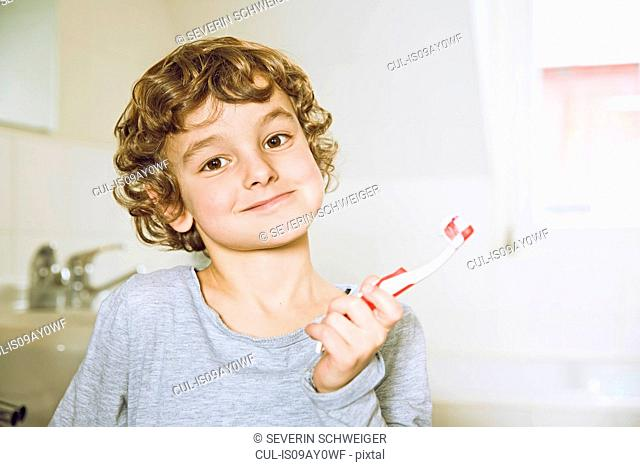 Boy in bathroom holding toothbrush looking at camera smiling